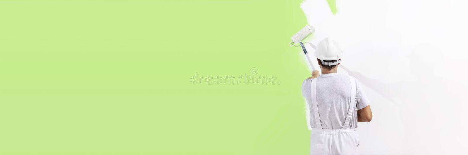 Painter man at work with a paint roller, wall painting green col royalty free stock photos