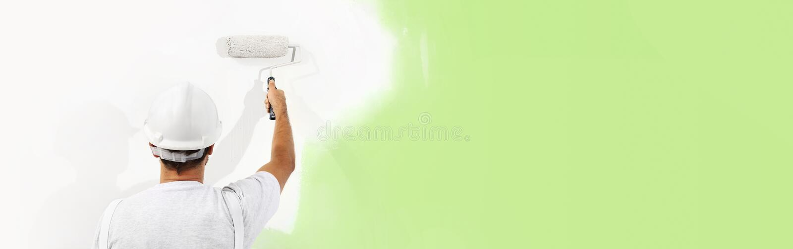 Painter man at work with a paint roller, wall painting green col. Or ecological concept, web banner template stock images