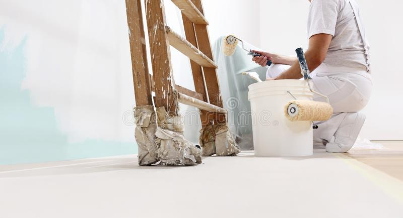 Painter man at work with a roller, bucket and scale, from below view, copy space stock photography