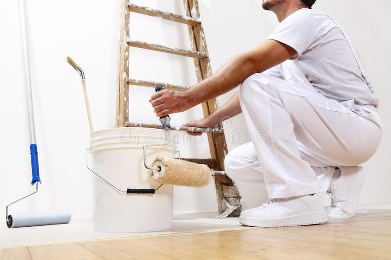 Painter man at work with a roller, bucket and scale royalty free stock images