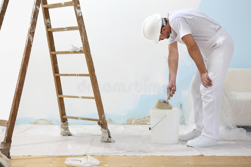 Painter man at work takes the color with paint brush from the bu stock images
