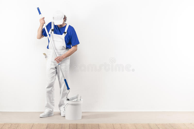 Painter man at work takes color with paint roller from the bucke royalty free stock photo