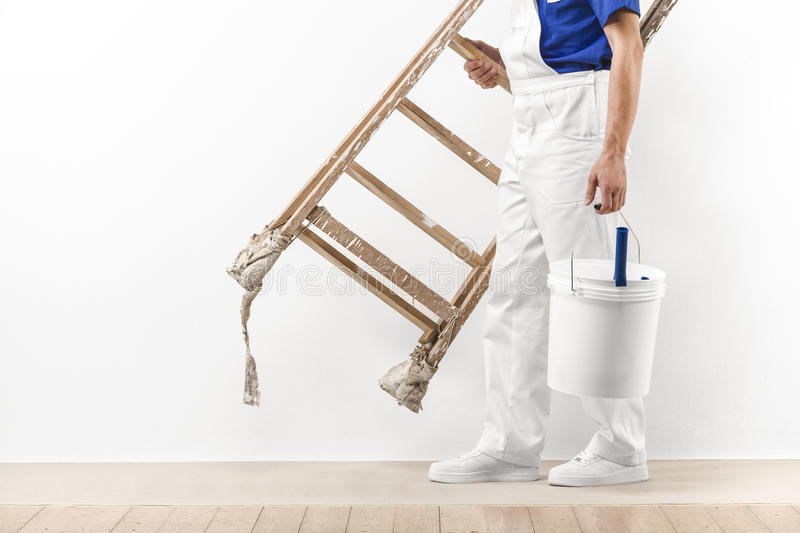Painter man at work with vintage ladder and bucket. royalty free stock photos