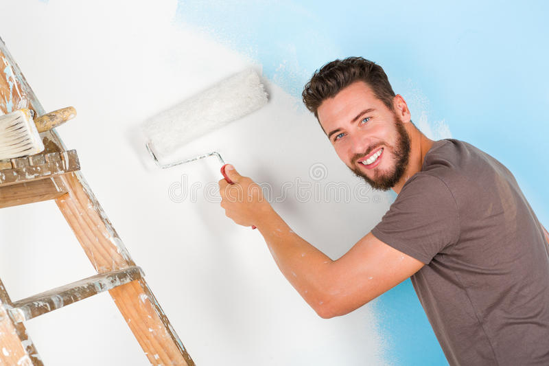Painter in paint splattered shirt painting a wall stock photography