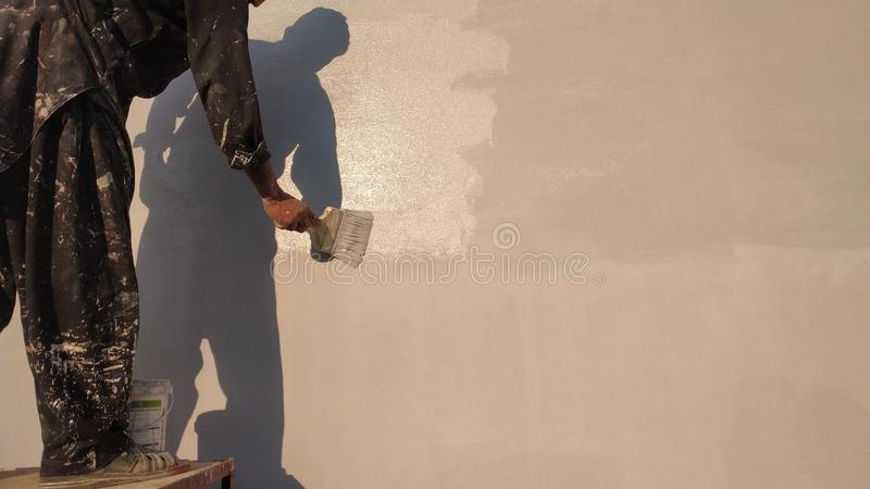 A painter painting with brush on wall. Shadow brushes  paint workers painting the wall painters brush roller shadows labour other new house decor decoration royalty free stock images