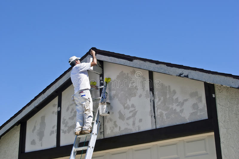Painter Painting a House. Painter on a ladder uses brown paint stock image