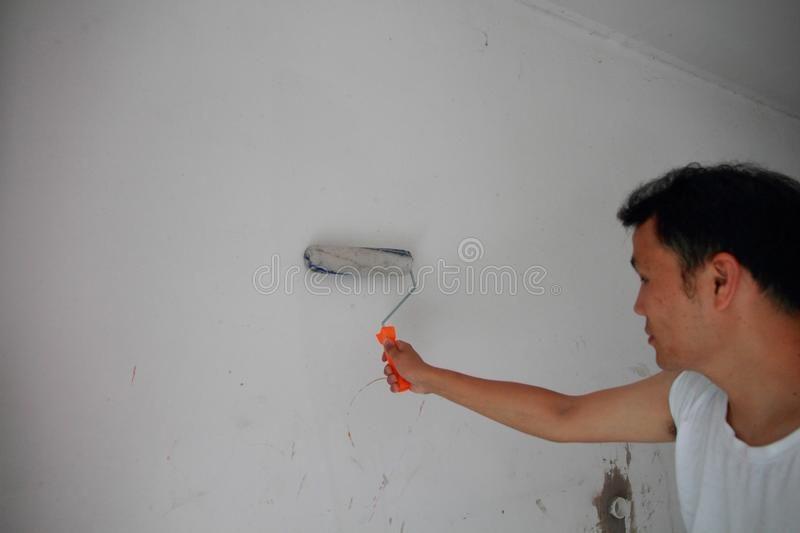 Painter Painting a House Wall with a Paint Roller. Painter hand holding a fabric roller and painting a house wall with satin finish white latex paint stock image