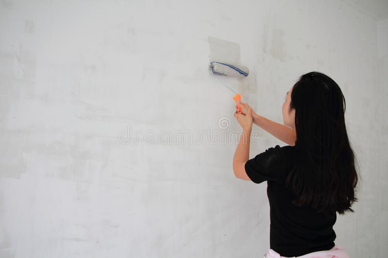 Painter Painting a House Wall with a Paint Roller. Painter hand holding a fabric roller and painting a house wall with satin finish white latex paint royalty free stock photo