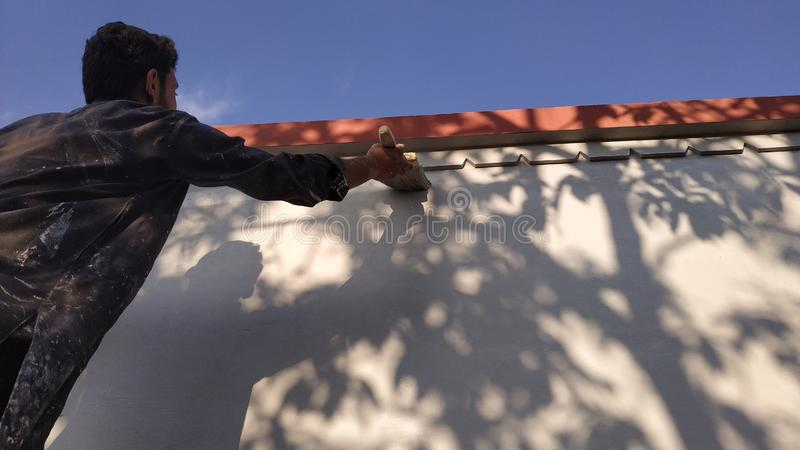 A painter painting the wall. Painter painting wall brush olor colour shadow man new home decor renovate renovation walls plant stock photo