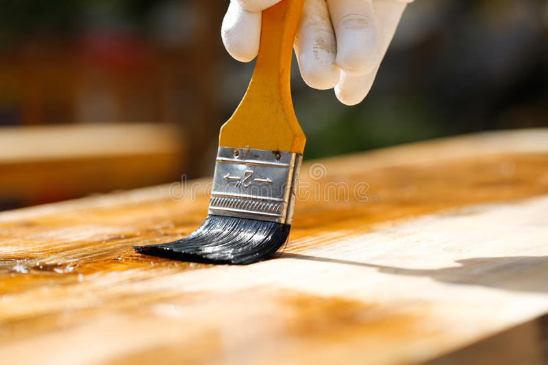 Painter painting wooden surface, protecting wood. Painter holding a paintbrush over wooden surface, protecting wood for exterior influences and weathering royalty free stock images