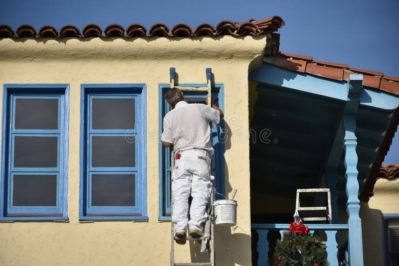 Painter, Painting a yellow and blue trimmed house royalty free stock image