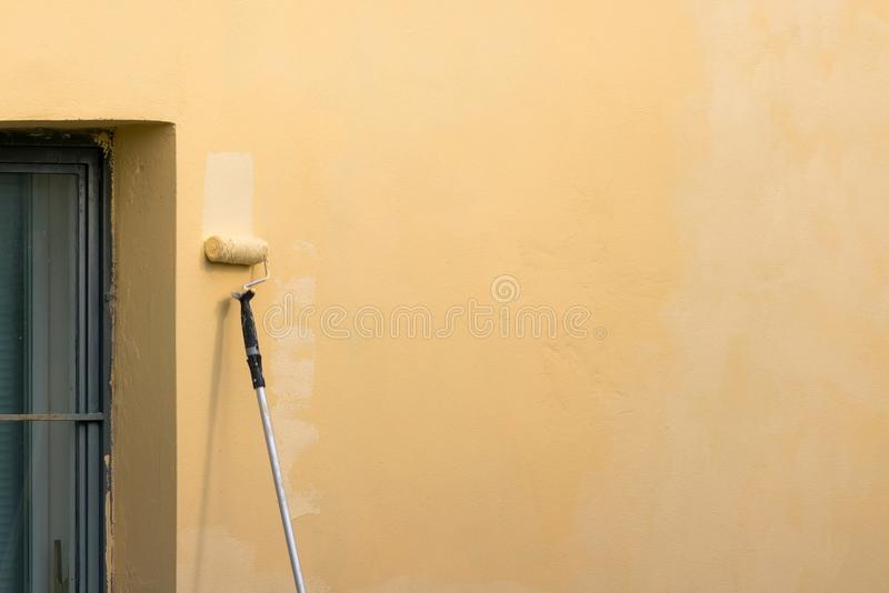 Painter paints building exterior wall with a roller. Roller with long stick manually painting building with yellow paint stock images