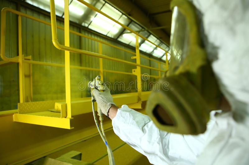 Industrial painting parts. The painter paints the iron element in yellow. The painter paints the iron element royalty free stock photography