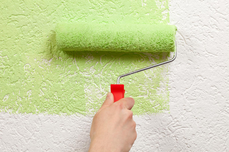 Painter paints a wall with a paint roller stock photography