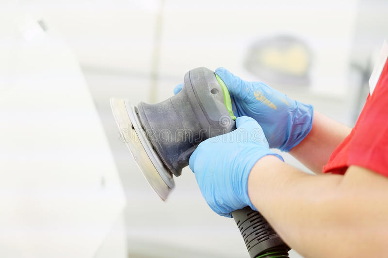 Painter polishes a car body. Component royalty free stock photography