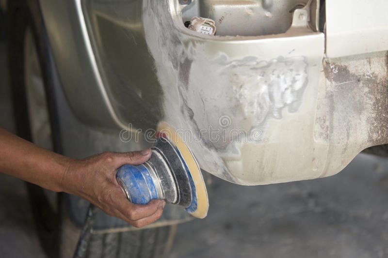 Painter polishes a car body component. Auto body repair stock images