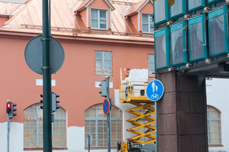 Painter with roller painting house facade in town stock image