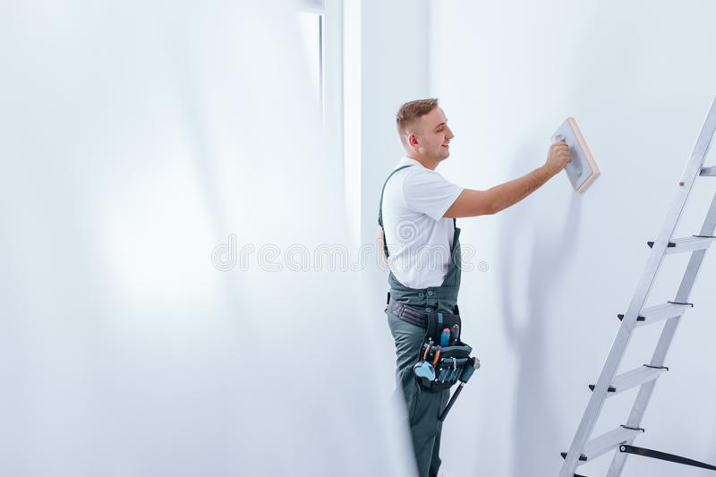Painter smoothing the wall stock photography
