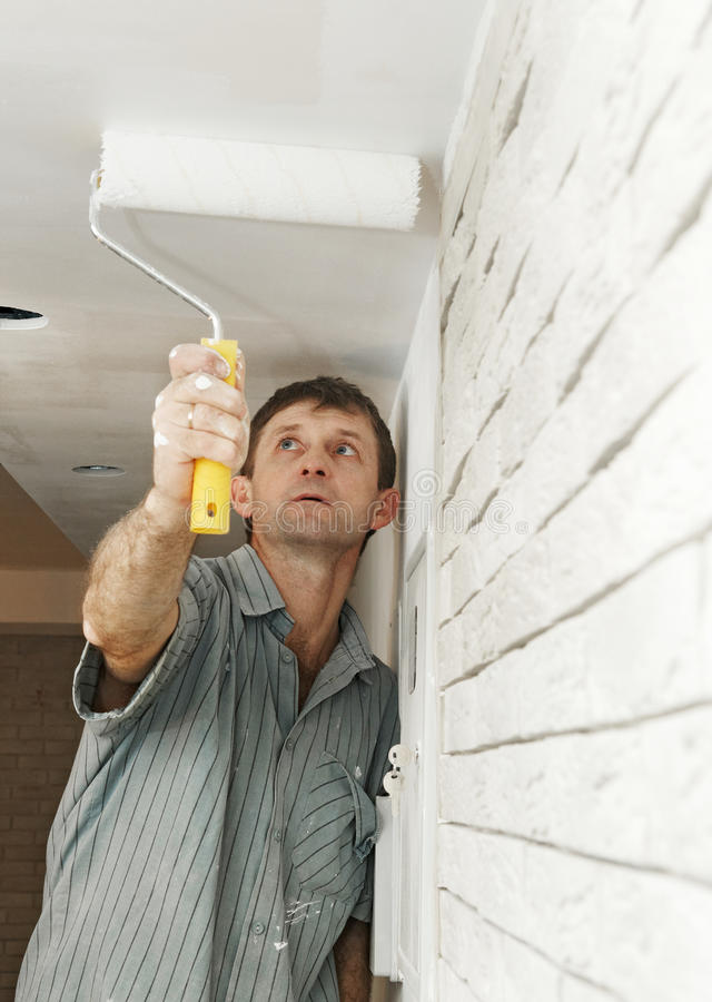 Painter worker painting a ceiling stock photography
