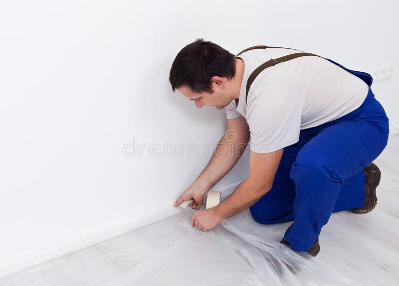 Painter worker preparing the room - laying protection film royalty free stock photography
