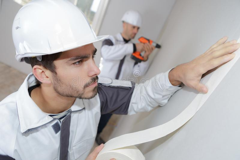 Painter worker protecting wall before painting at home improvement work. Builder stock images
