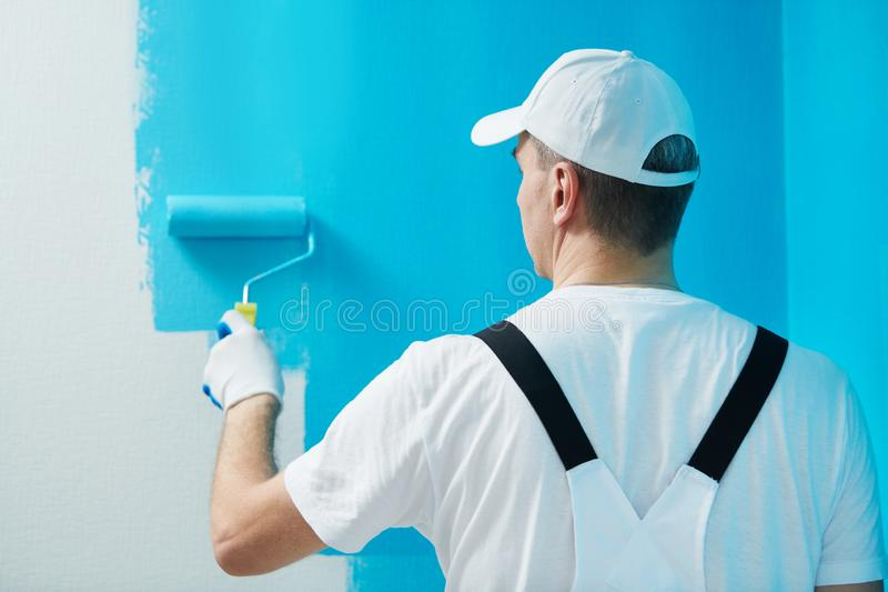 Painter worker with roller painting wall surface into color stock image