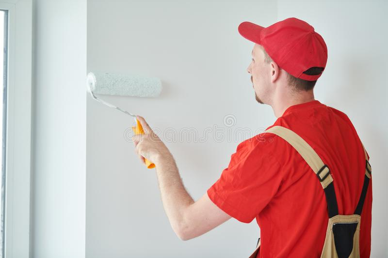Painter worker with roller painting wall surface into white royalty free stock photo