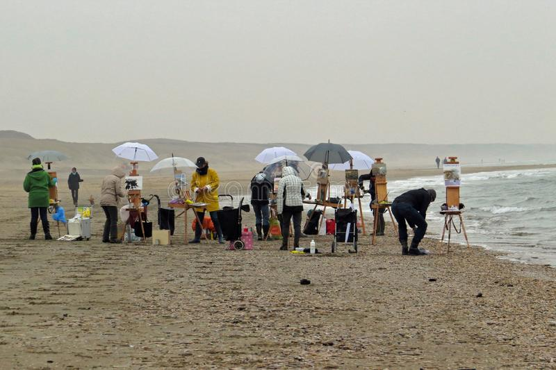 Painters / artists with their easels painting at the foggy beach in Katwijk, Netherlands royalty free stock image
