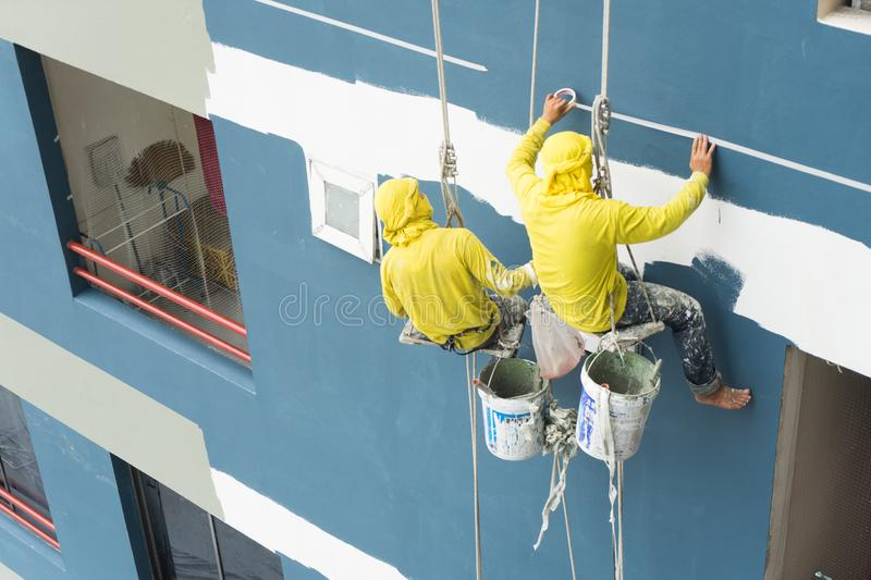 Painters hanging on roll, painting color on building wall. Facade builder worker with roller brush, working on high building..safety construction with lift stock image