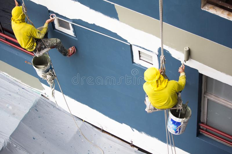 Painters hanging on roll, painting color on building wall. Young painting facade builder worker with roller brush, working on high building, working together royalty free stock images