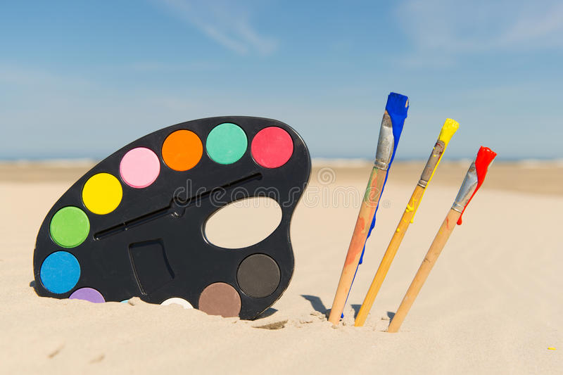 Painters palette in landscape. Colorful Painters palette with brushes at the beach stock photos