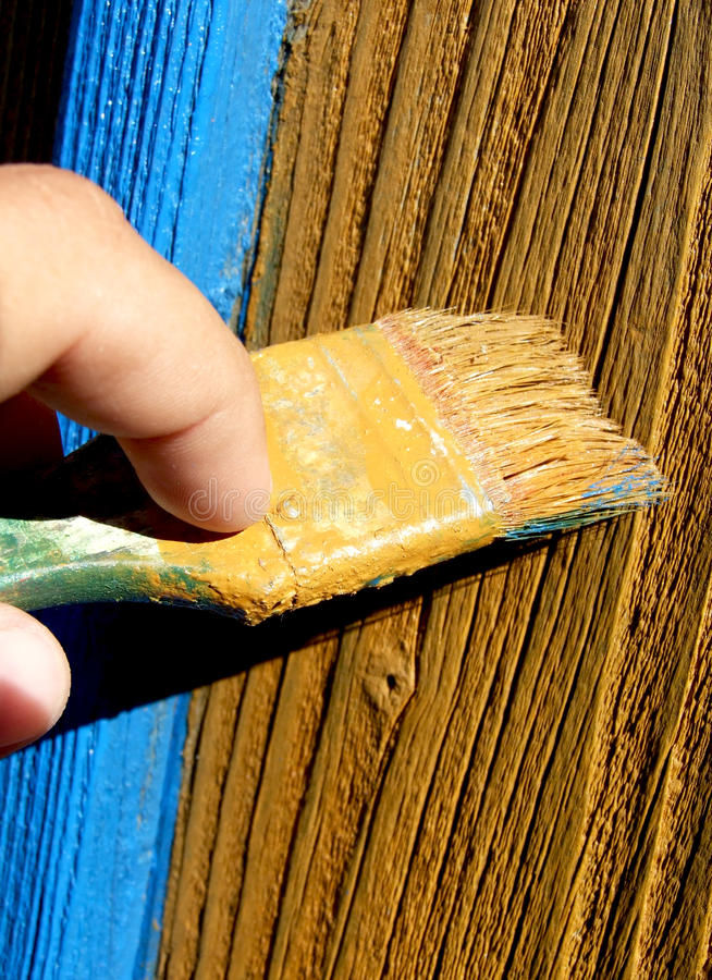 Painting. Man's hand painting a wood surface stock photo