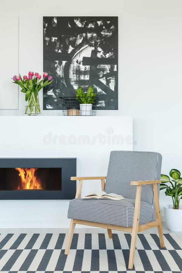Painting above fireplace in modern living room interior with pat. Terned armchair on carpet. Real photo concept royalty free stock image