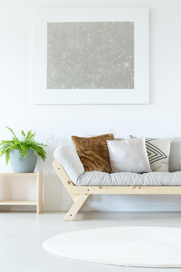 Painting above grey chaise lounge. Silver painting above grey chaise lounge with brown pillow and plant in blue pot in simple living room royalty free stock photo