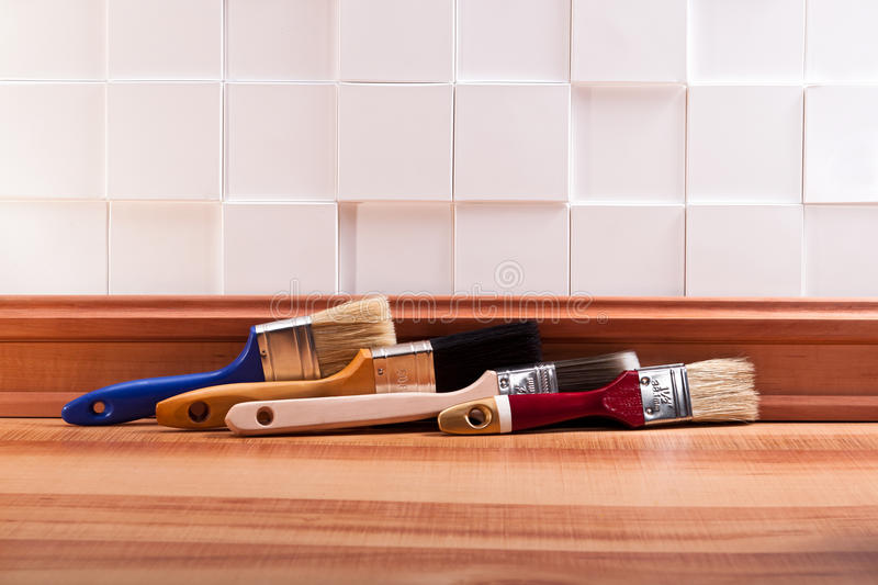 Painting in the apartment. Paint brush on the parquet floor with a decorative wall stock photo