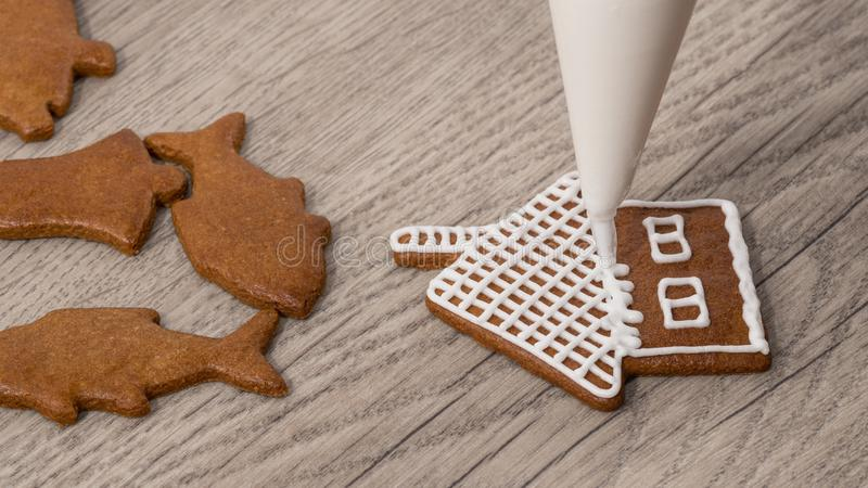 Close-up of decorating a christmas gingerbread in cottage shape royalty free stock photos