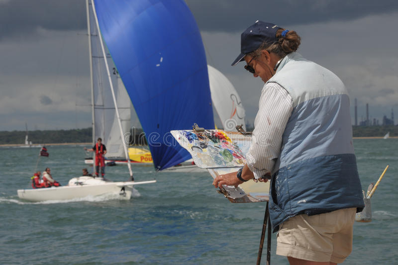 Marine artist painting yachts. Marine artist Hilary Thorpe at work by the waters edge of the Solent during international sailing events Cowes Week. Isle of Wight royalty free stock image