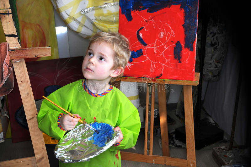 Painting boy. Four years old toddler boy painting at easel in an art studio royalty free stock images