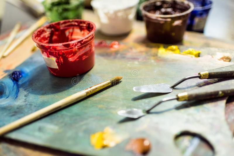 painting brushes, palette and poster paints on wooden table royalty free stock images