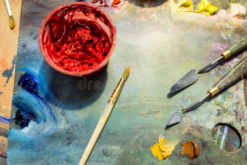 Painting brushes, palette and red poster paint on wooden table. In workshop stock photo
