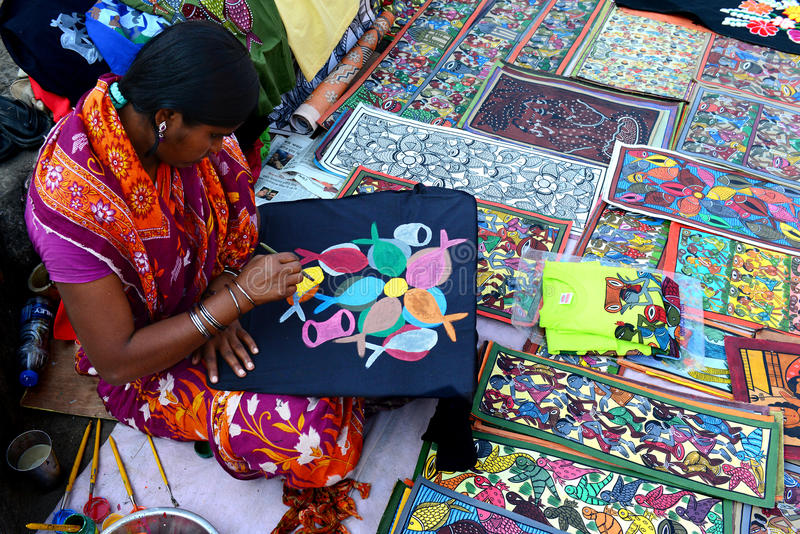 Painting Business. A woman artist doing folk painting for sale at the Handicraft Fair of Kolkata royalty free stock photography