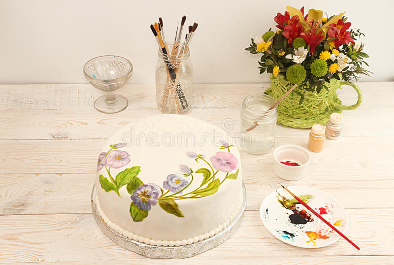 Painting cake with food colorings. Cake with pansies. Painting cake with food colorings. Round cake with fondant and painted flowers. Cake with pansies royalty free stock photos