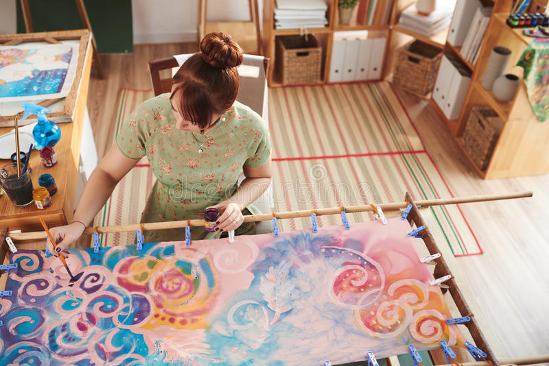 Painting on canvas. Female artist painting on stretched canvas alone stock photo