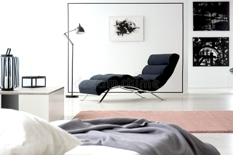 Painting and chaise lounge. Black and white painting on the wall and comfy chaise lounge next to a lamp in a bedroom interior stock photos