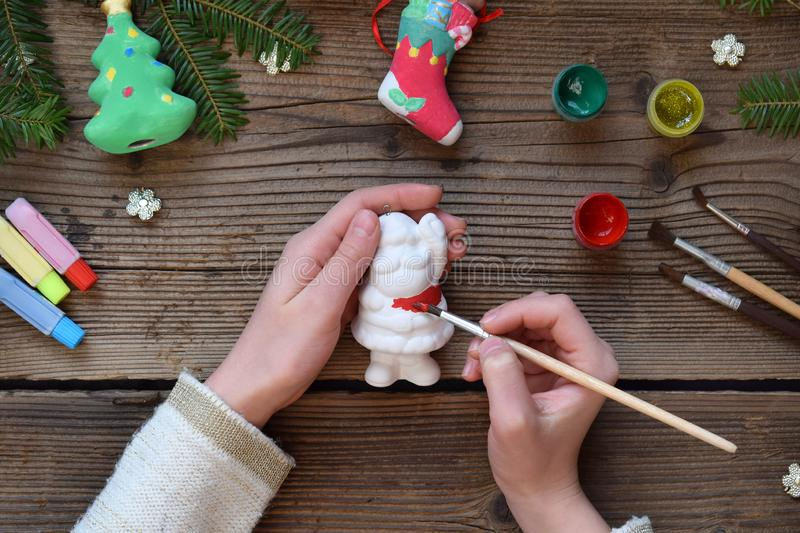 Painting Christmas toys from porcelain for decorations. Making clay toy with your own hands. Children& x27;s DIY concept. Handmade stock photography