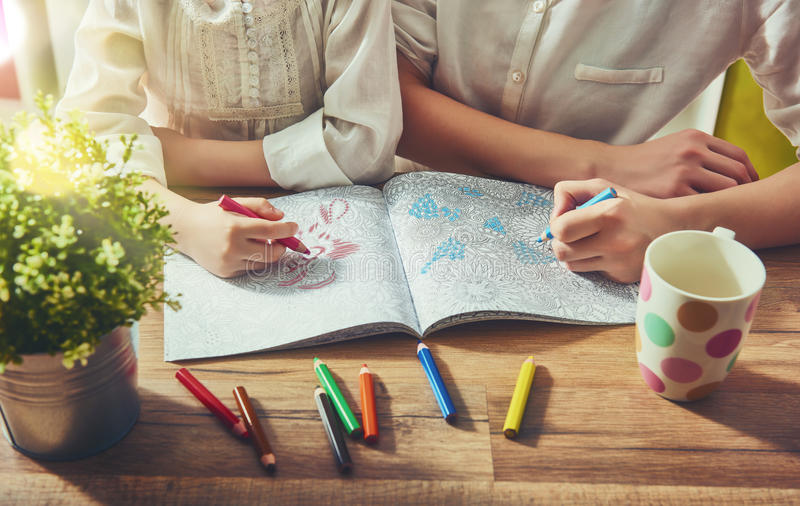Painting a coloring book. Child and adult are painting a coloring book. New stress relieving trend. Concept mindfulness, relaxation royalty free stock images
