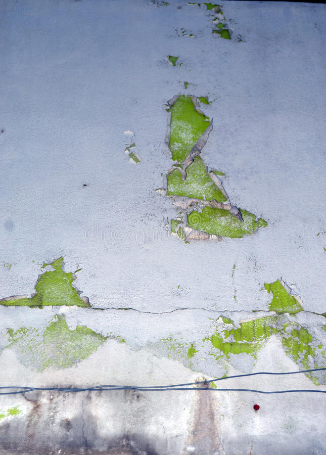 PAINTING COUNTERFEIT. View of the facade of an exterior wall of a house degraded because of the counterfeiting of the paint that has given way to the various stock photo