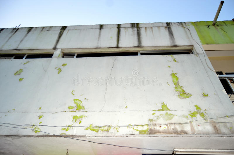 PAINTING COUNTERFEIT. View of the facade of an exterior wall of a house degraded because of the counterfeiting of the paint that has given way to the various stock image