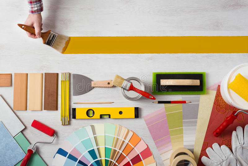Painting and decorating DIY banner. Decorator holding a paint brush and painting a wooden surface, work tools and swatches at bottom, banner with copy space royalty free stock image