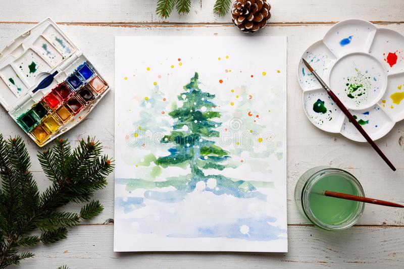 Painting a DIY Christmas card with watercolor royalty free stock photo